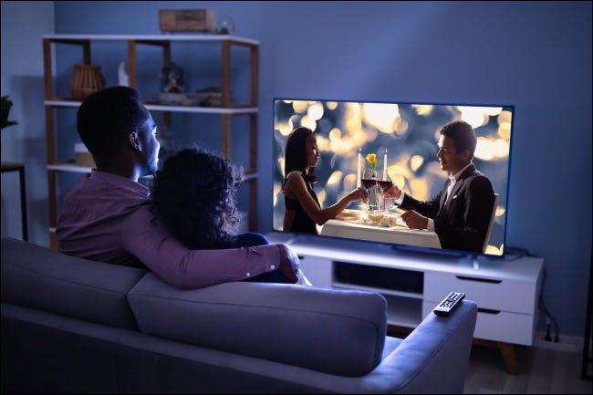 Una pareja viendo la televisión en un sofá.