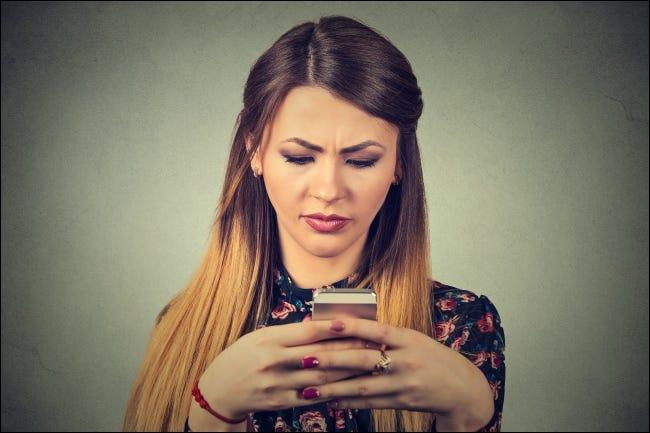 Una mujer infeliz mirando un teléfono inteligente.