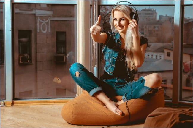 Una mujer escuchando con auriculares y dando un pulgar hacia arriba.