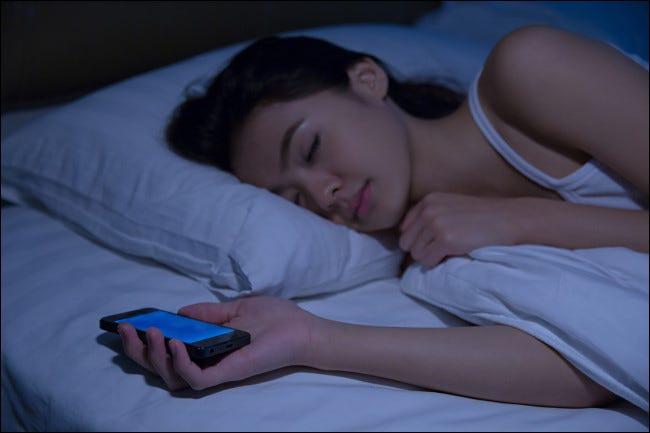 Una mujer durmiendo mientras sostiene un teléfono inteligente.