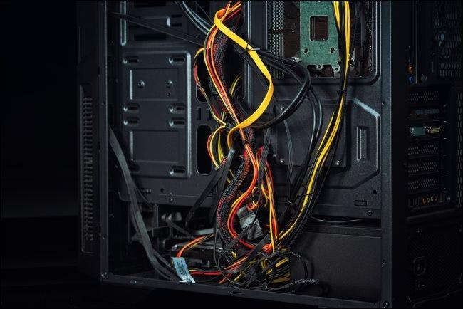 Gestión de cables defectuosa y desordenada dentro de una carcasa de PC.